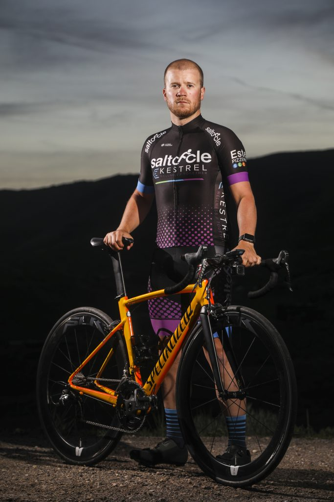 Sawyer Pangborn standing behind a bicycle wearing SaltCycle-Kestrel Wellness cycling kit.