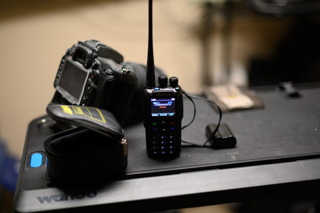Photo of a handheld amateur radio unit and a Nikon DSLR
