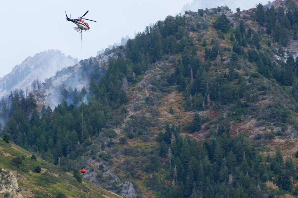 An aerial firefighting helicopter, N357TA, flies over the Neff's Fire in Neff's Canyon just east of Millcreek, Utah.
